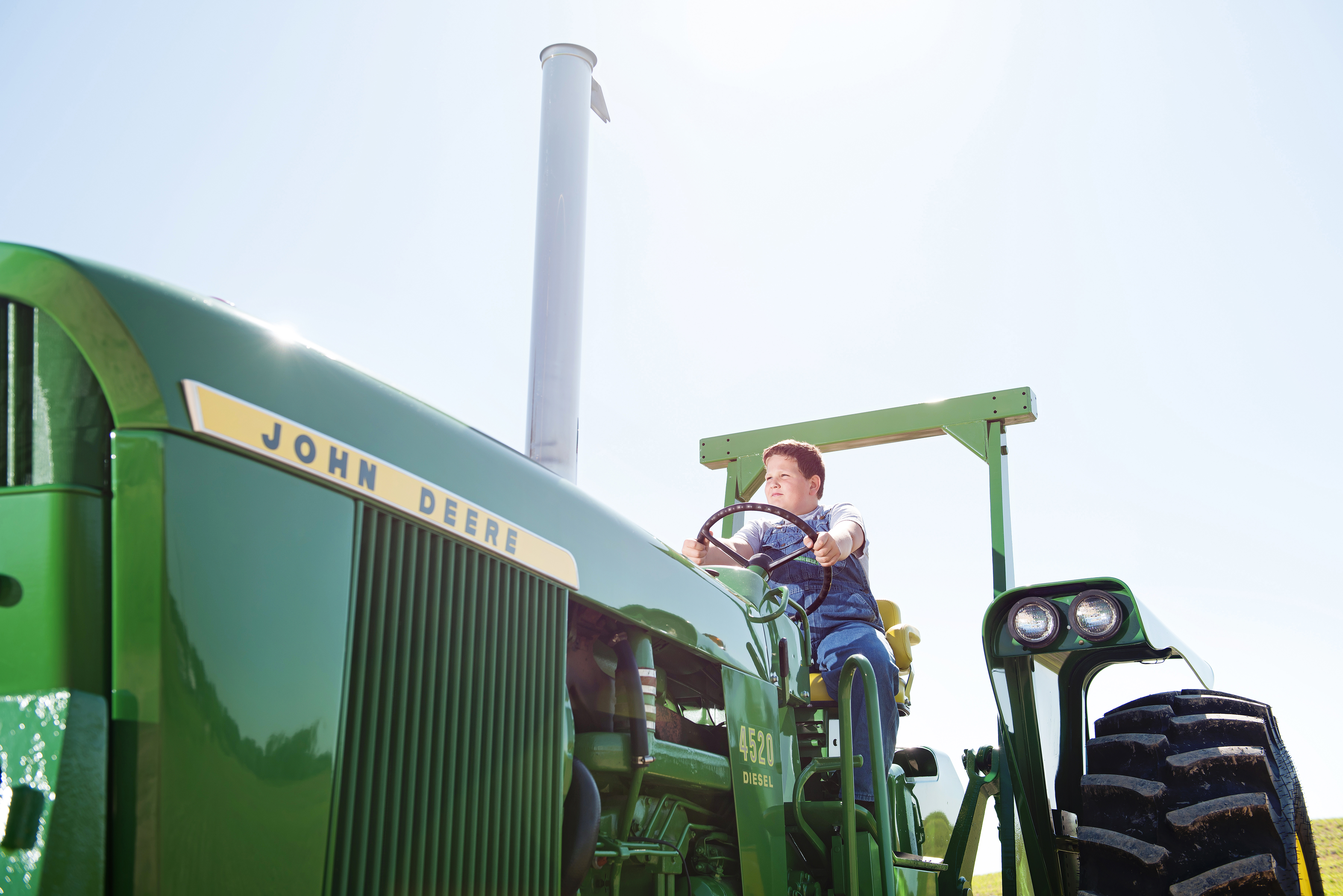 A boy plays on a tractor on a farm near Red Ring, Minnesota.