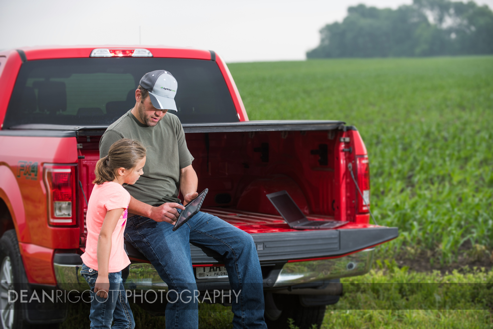 Working in the field with his daughter and an ipad on the fmaily farm in Medford, Minnesota.