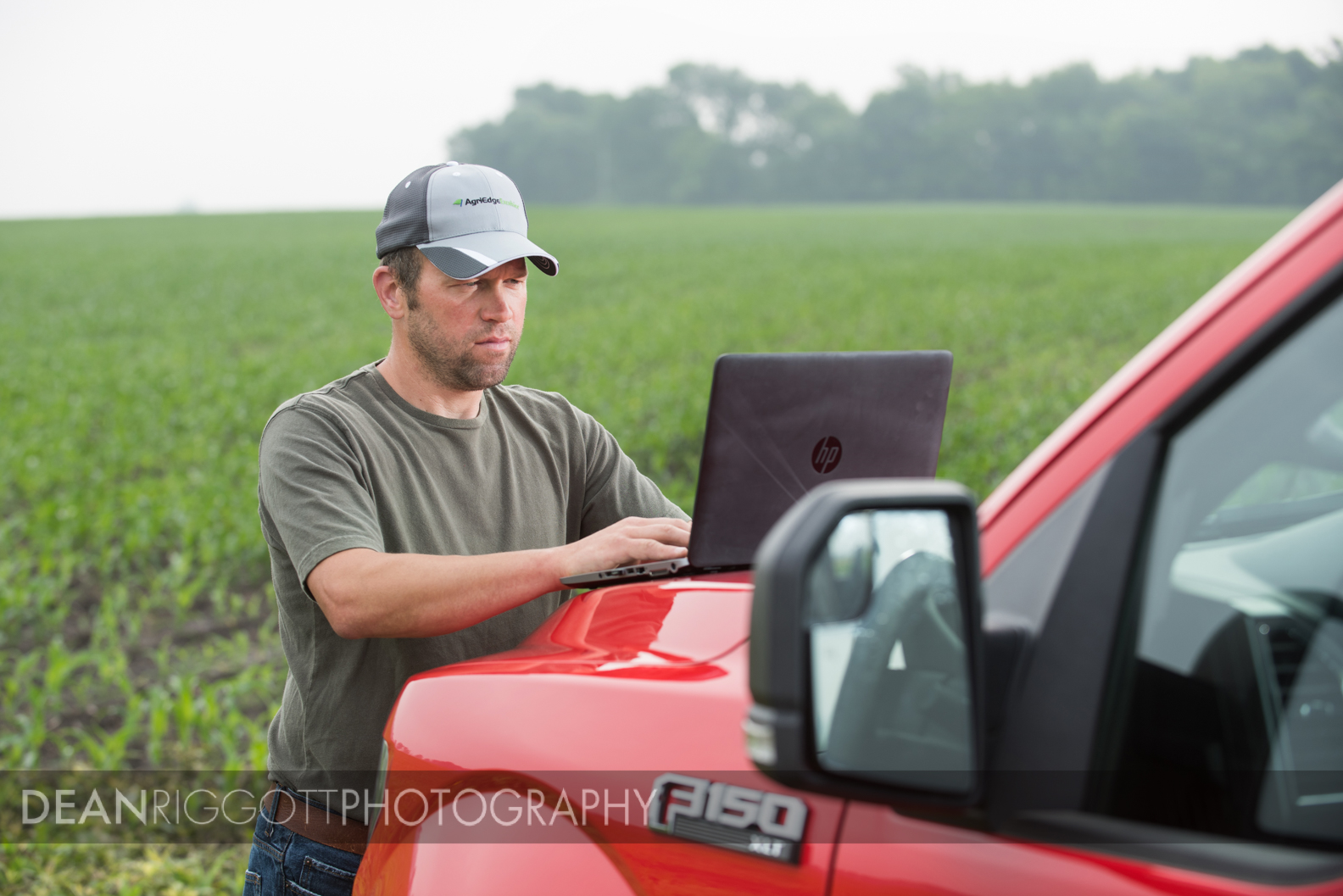 Working in the field with hi a laptop on the family farm in Medford, Minnesota.